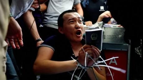 Szene aus dem Flughafen Hongkong am 13. August. Der von den Demonstranten festgehaltene Reporter Fu Guohao zeigt seinen Pass. Sie werfen ihm vor, sich als Spion vom chinesischen Festland unter die Demonstranten gemischt zu haben.