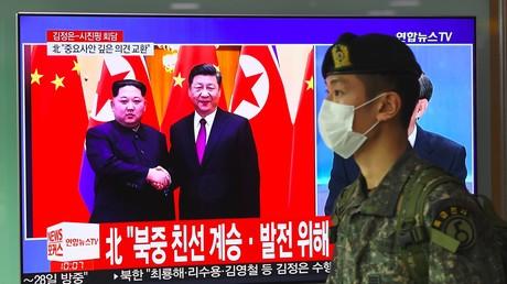 Ein südkoreanischer Soldat geht an einem Fernseher vorbei, der über einen Besuch des nordkoreanischen Führers Kim Jong Un in China am 28. März 2018 auf einem Bahnhof in Seoul berichtet.
