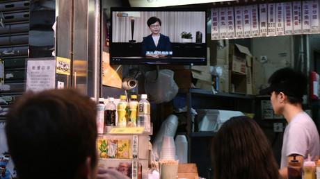 Besucher eines Imbisses in Hongkong schauen die TV-Ansprache von Carrie Lam an, wo sie einen Teil der Forderungen der Protestler erfüllt.