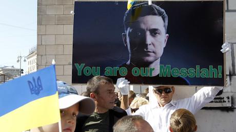 Nach drei Monaten im Amt ist Präsident Wladimir Selenskij immer noch Hoffnungsträger vieler Ukrainer. Auf dem Bild: Ein Mann hält ein Pro-Selenskij-Plakat während der Feierlichkeiten am Tag der Unabhängigkeit am 24. August.