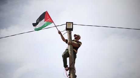 Ein Mann platziert eine palästinensische Flagge an einem Strommast, Gazastreifen, 28. März 2018.
