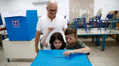 Ein Mann und zwei Kinder stehen am 17. September 2019 vor einer Wahlurne in einem Wahllokal in Tel Aviv, Israel, und geben eine Stimme ab. Rund 6,3 Millionen Menschen sind aufgerufen, die 120 Mitglieder der 22. Knesset in Jerusalem zu bestimmen.