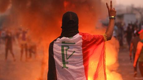 Ein in eine irakischen Flagge gehüllter Demonstrant, zeigt am 2. Oktober auf dem Tajaran-Platz in Bagdad das Friedenszeichen.