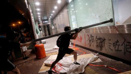 Ein Demonstrant bei dem Versuch, das Fenster einer Metrostation in Hongkong zu zerstören, 6. Oktober 2019