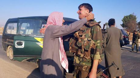 Ein Einwohner der Ortschaft Tell Tamer begrüßt einen syrischen Soldaten. Nach der Einigung mit der kurdisch-dominierten SDF rückte das syrische Militär in Nordsyrien vor.