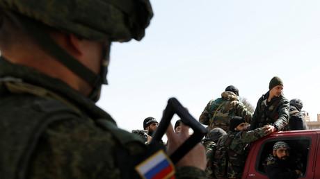 Symbolbild: Ein russischer Soldat blickt auf eine Gruppe syrischer Soldaten an einem Kontrollpunkt nahe dem Wafideen-Camp in Damaskus. (2. März 2018)