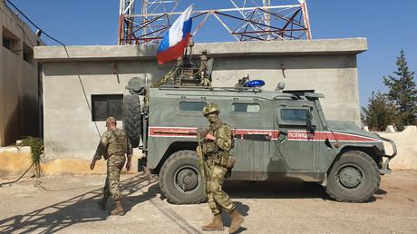 Russische Soldaten laufen an einem Einsatzwagen der russischen Militärpolizei in der Stadt Ain-al Arab (Kobanê) vorbei (Bild vom 23. Oktober).