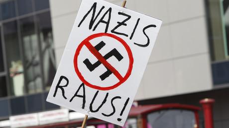 Ein Demonstrant hält bei einer Kundgebung gegen Rechts ein Schild, auf dem