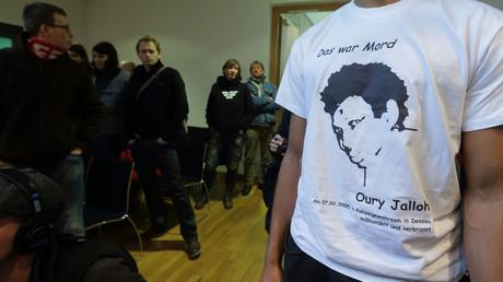 Ein Mann im T-Shirt mit dem Bild des Asylbewerbers Oury Jalloh aus Sierra Leone während des Prozesses gegen den Polizisten Andreas S. am 13. Dezember 2012 vor dem Landgericht Magdeburg