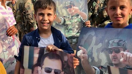 Assad im Interview: Sanktionen zielen auf die Bürger ab und sollen einen Regimewechsel antreiben (Symbolbild: Kinder mit Portraits des syrischen Präsidenten Baschar al-Assad in Manbidsch nach der Befreiung der Stadt durch die Syrische Arabische Armee, 15. Oktober 2019)