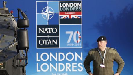 Ein britischer Soldat steht vor einem NATO-Plakat in Watford, wo das