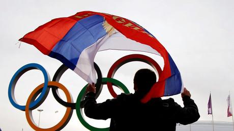 Ein Mann mit russischer Flagge vor den Olympischen Ringen, Sotschi, Russland, 22. Februar 2014.
