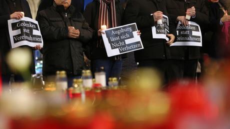 Teilnehmer einer Trauerfeier in Augsburg warnen auf Schildern vor einer politischen Instrumentalisierung des Verbrechens (9. Dezember 2019).