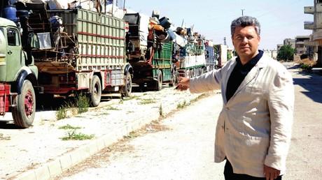 Waffenverkauf an IS, Mord, Raub - US-gestützte Miliz machte syrisches Flüchtlingslager zu Gefängnis (Maxim Grigorjew, Leiter der Stiftung zur Erforschung von Problemen der Demokratie, vor Kolonne von Flüchtlingsfahrzeugen am Erstaufnahmepunkt. Bild aus dem Bericht der NGO zum Lager Rukban)