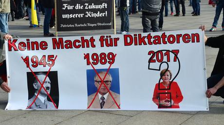 Rechtsextreme Demonstranten halten Banner mit den Slogans