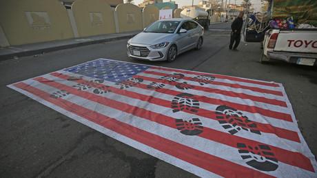Nachdem sich die Nachricht vom Tod von Qassem Soleimani und Abu Mahdi al-Muhandis wie ein Lauffeuer verbreitet hat, wurde in Bagdad eine US-Flagge auf die Straße gelegt, über die Autos fahren sollen.