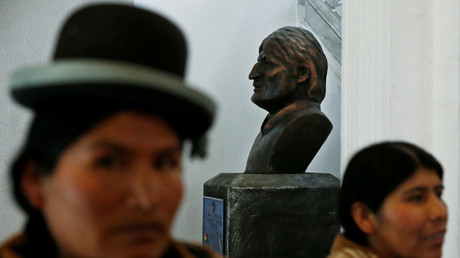 Frauen der indigenen bolivianischen Mehrheitsbevölkerung stehen im Kongressgebäude in La Paz vor einer Büste des gestürzten Präsidenten Evo Morales