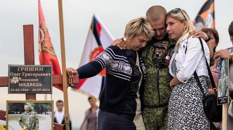 Angehörige und ein Kampfkamerad trauern am Ort der Kämpfe bei Sayr Mogila vor dem Grab eines Mitglieds der Donezker Volksmiliz, Mai 2015. Schätzungen zufolge zählen die Rebellen in der Ostukraine über 6.000 Toten. Die Gesamtzahl der Todesopfer im Donbass-Krieg beträgt mehr als 13.000.