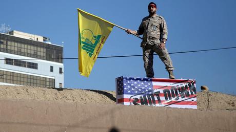 Eine iranische Wache hält eine Hisbollah-Flagge während des Trauerzuges bei der Beerdigung von Soleimani in Kerman und steht dabei auf einer US-Flagge. Auf dieser steht: