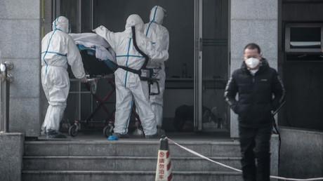 18. Januar 2020: Mediziner tragen einen Patienten in ein Krankenhaus, wo Menschen behandelt werden, die mit dem mysteriösen Virus infiziert sind
