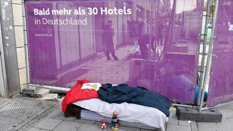 Schlafplatz eines Obdachlosen in München vor Sichtschutz-Reklame für Hotelkette, November 2019