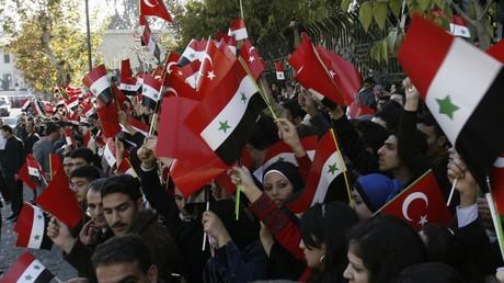 Damaszener mit den Fahnen der Türkei und Syriens während eines Besuchs des syrischen Präsidenten Baschar al-Assad und des damaligen türkischen Ministerpräsidenten Recep Tayyip Erdoğan, Dezember 2009.