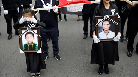 Ein geflüchtetes nordkoreanisches Mädchen und ihre Mutter tragen Porträts eines toten Jungen aus Nordkorea und dessen Mutter vor sich her, Seoul, Südkorea, 21. September 2019.