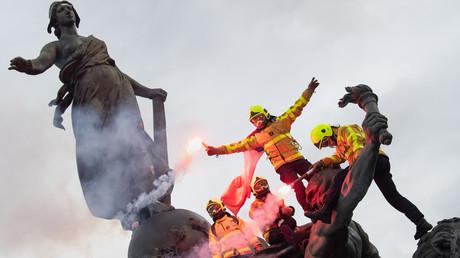 Französische Feuerwehrmänner mit einer roten Fahne schwingen Fackeln, während sie auf die Statue des