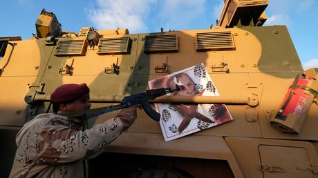 Ein Kämpfer der Libyschen Nationalarmee von General Chalifa Haftar zeigt mit seiner Waffe auf ein türkisches Panzerfahrzeug, das sie bei Kämpfen in Tripolis erobert haben wollen (Bild vom 28. Januar).