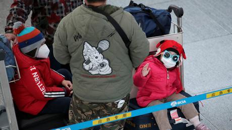 Kinder mit Schutzmasken am 1. Februar 2020 auf dem internationalen Flughafen von Peking. Hintergrund ist der Ausbruch des neuartigen Coronavirus in China.