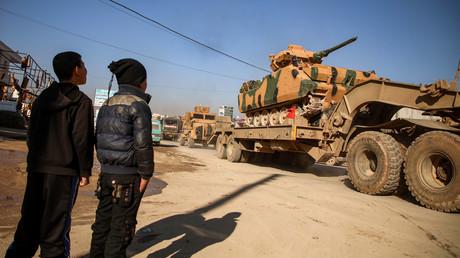 Jungen in der syrischen Stadt Dana beobachten die Verlegung von türkischem Kriegsgerät in die Provinz Idlib am 2. Februar.