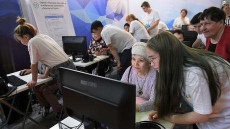Studenten bringen den Rentnern die Nutzung des Portals für Staatliche Dienste auf dem XI. Internationalen IT-Forum mit Beteiligung von SOZ und BRICS-Ländern in Chanty-Mansijsk, Juni 2019.