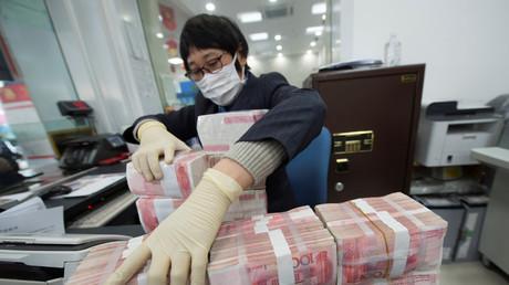 Bankmitarbeiter mit Gesichtsmaske ordnet Yuan-Banknoten