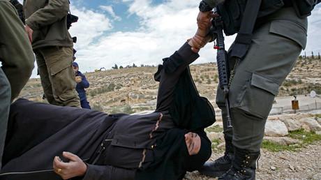 Ein israelischer Soldat zieht eine palästinensische Frau auf dem Boden, nachdem das Haus ihrer Familie in dem Dorf Al-Dirat in der Nähe von Hebron am 16. Januar durch Israel zerstört wurde, weil es angeblich ohne israelische Genehmigung gebaut wurde.
