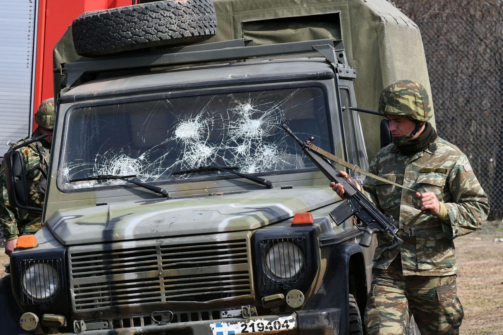 Ein griechischer Soldat steht neben einem Armeefahrzeug mit zerbrochener Windschutzscheibe