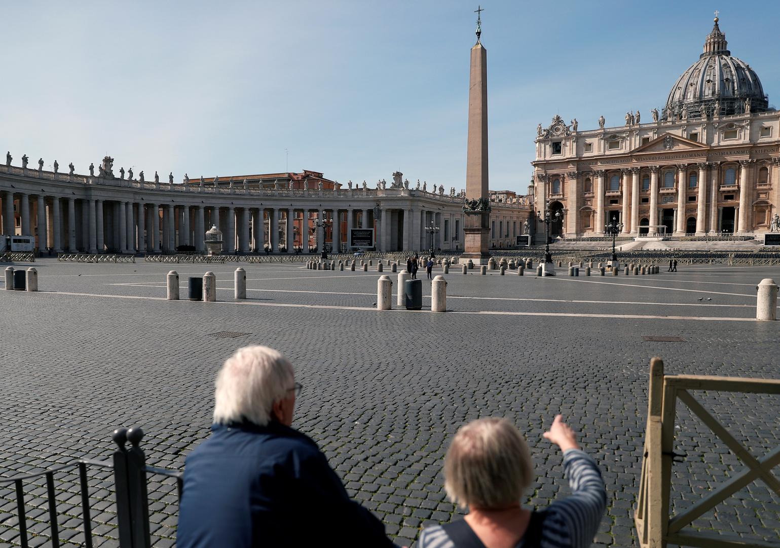 Ein Ehepaar betrachtet den menschenleeren Petersplatz, nachdem in Rom eine Ausgangssperre verhängt wurde