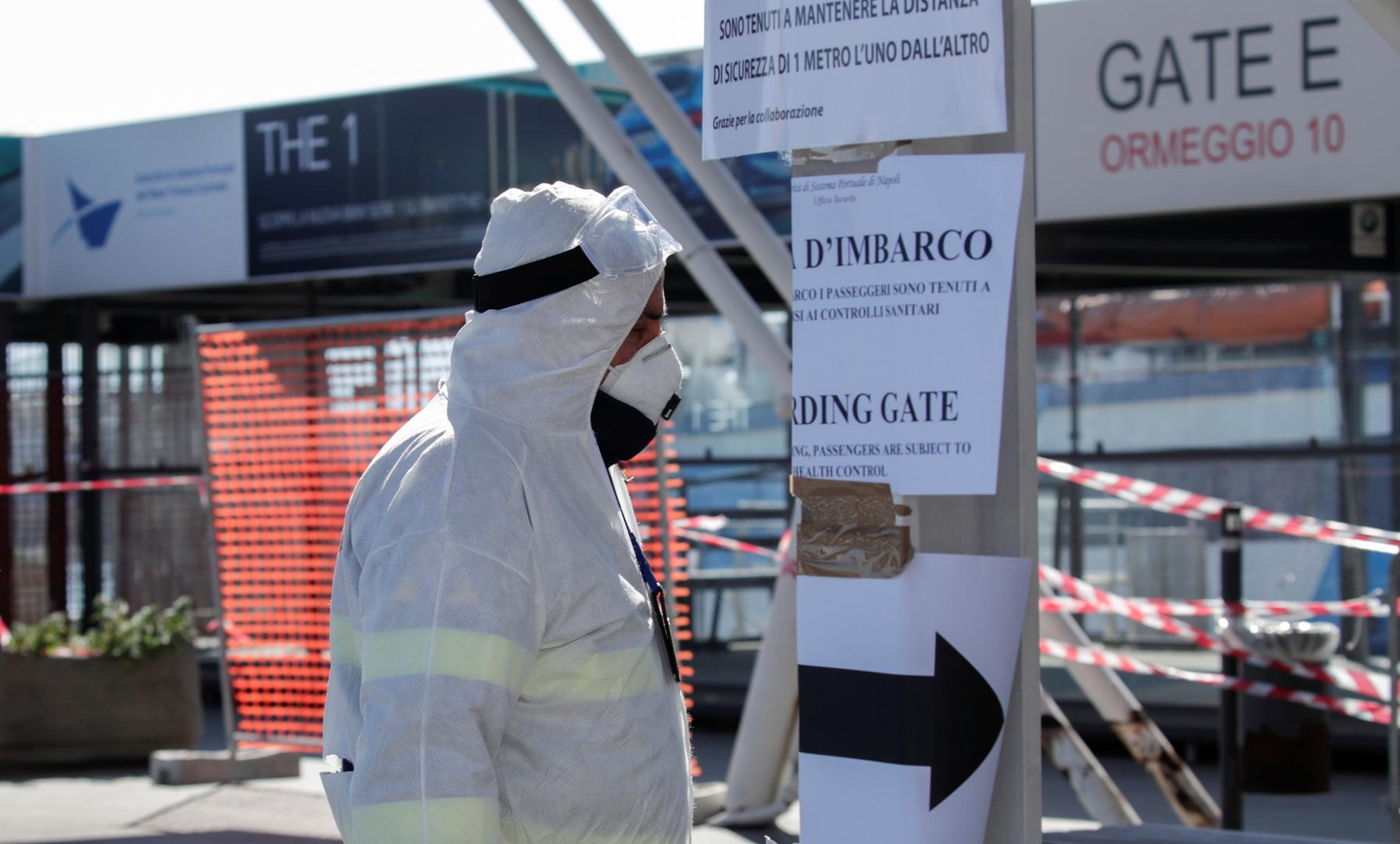 Ein Beamter im Schutzanzug während der Kontrolle von Körpertemperatur bei Passagieren im Fährhafen von Molo Beverello in Neapel