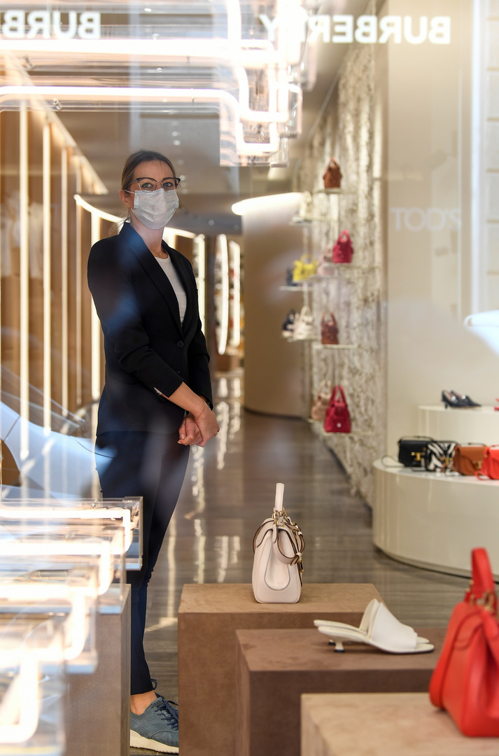 Eine Frau trägt eine schützende Gesichtsmaske in einem Geschäft in Mailand