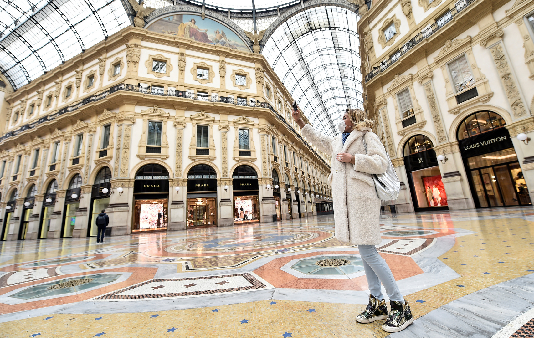 Eine Frau mit einer schützenden Gesichtsmaske schießt in der menschenleeren Galleria Vittorio Emanuele II Selfies, nachdem in Mailand ein Dekret erlassen wurde, das ganz Italien zu einem beispiellosen Vorgehen gegen das Coronavirus zwingt.