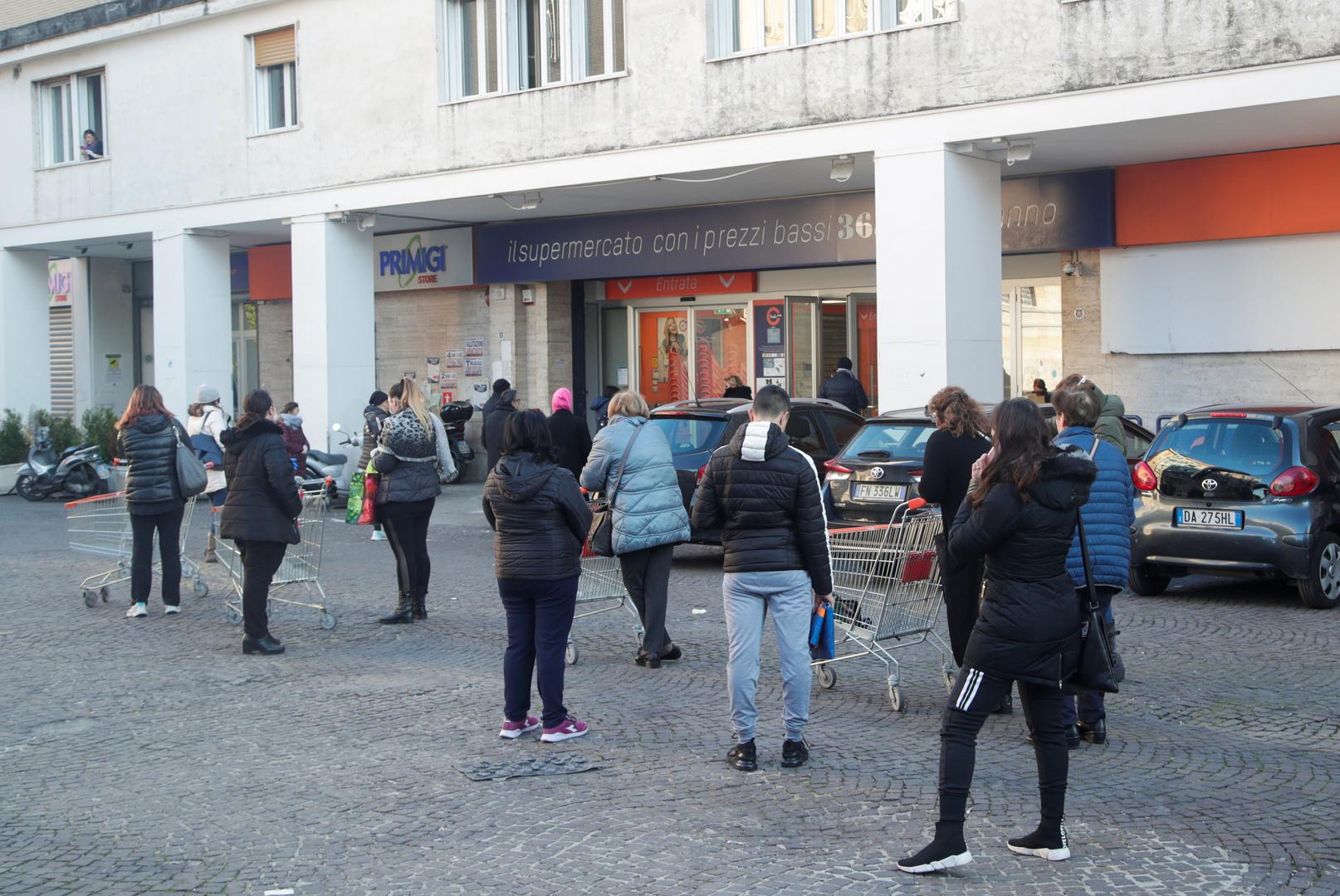 Menschen warten in der Schlange, um Lebensmittel und Waren zu kaufen, nachdem  in Neapel eine Ausgangssperre verordnet wurde