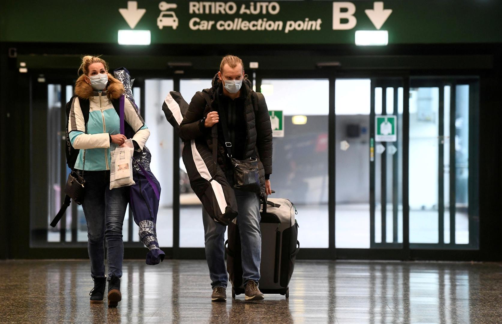 Menschen mit Schutzmasken gehen auf dem Flughafen Malpensa bei Mailand