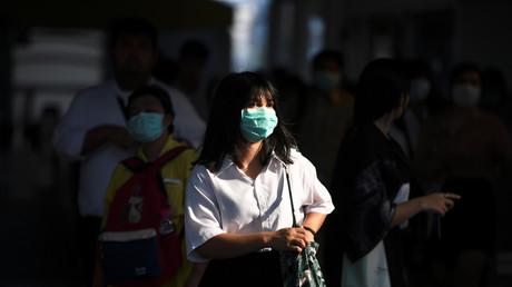 Eine Frau mit einer schützenden Gesichtsmaske geht in Bangkok