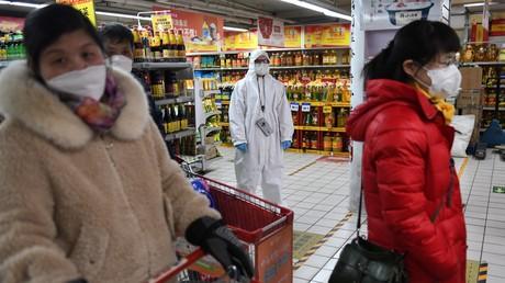 Eine Mitarbeiterin in einem Supermarkt in Peking trägt Schutzanzug und Mundschutz (Bild vom 3. März) aus Angst vor einer Ansteckung mit dem Corona-Virus.