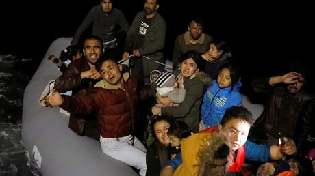 Migranten winken und rufen nach einem gescheiterten Versuch, die griechische Insel Lesbos zu erreichen, während sich ihnen ein Schiff der türkischen Küstenwache nähert.