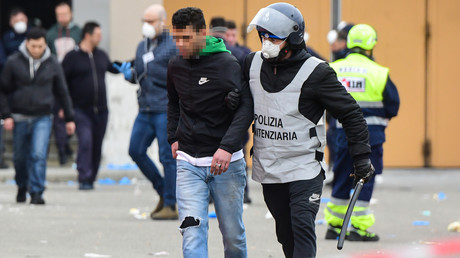 Ein Insasse im Sant'Anna-Gefängnis in Modena wird von einem Wärter eskortiert, nachdem es zuvor zu einem Aufstand aufgrund von geänderten Besuchsregeln gekommen war.