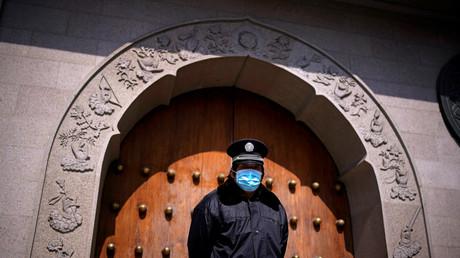 Ein Sicherheitsmann mit Gesichtsmaske vor einem geschlossenen Tempel, 6. März 2020 in Shanghai, China.