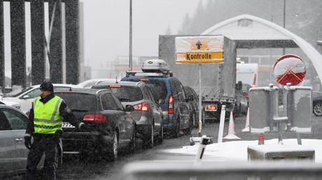 Ein Polizist steht am 10.03.2020 neben einer Autokolonne am Brennerpass zwischen Italien und Österreich. Ab sofort will Österreich wegen der Ausbreitung des Coronavirus an der Grenze zu Italien die Temperatur von Reisenden kontrollieren.