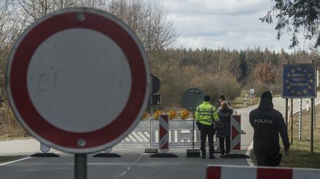 Ein tschechischer Grenzbeamter spricht mit deutschen Passanten, die am Samstag mit ihrem Hund über den Grenzübergang Mähring-Broumov in die Tschechische Republik spazieren wollten. (Bild vom 14. März)
