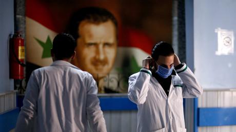 In einem Hospital in Damaskus zieht ein Krankenhausmitarbeiter eine Schutzmaske über. Nach neun Jahren Krieg könnte das Coronavirus das Land nun doch noch in die Knie zwingen.