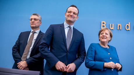 Lothar Wieler, Präsident des Robert-Koch-Instituts, Gesundheitsminister Jens Spahn und Bundeskanzlerin Angela Merkel zeigen sich gut gelaunt vor einer Pressekonferenz, bei der Merkel verkündete, dass sich zwei Drittel der Deutschen mit dem Coronavirus infizieren könnten. (Berlin, 11. März 2020)-
